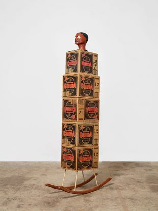 """Image Credit: Henry Taylor, Rock It, (2008). 5 cardboard boxes (premium malt boxes), acrylic on foam mannequin head, wood) 36"""" x 12"""" x 80 1/2"""". © Henry Taylor"""